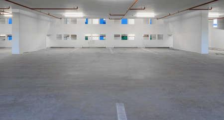 Indoor empty parking lot illuminated at night photo