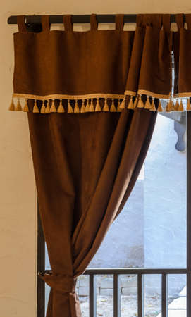 yellow tassel: Glass window with brown velvet curtain
