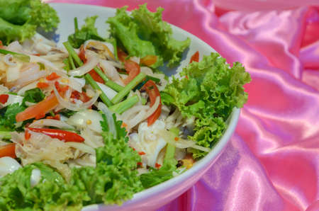 Thai spicy and sour seafood salad in a plate on pink fabric photo