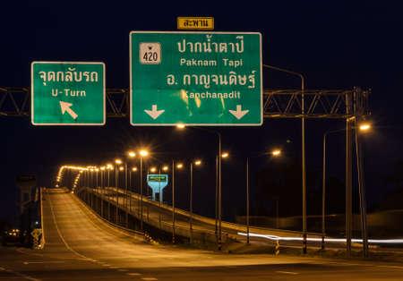 thani: Thai road signboard with bridge at night in Surat Thani Thailand. Si Surat bridge is crossing bridge of Tapi river.