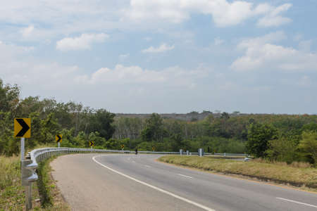 curve road: Countryside road with barrier and warning curve road sign