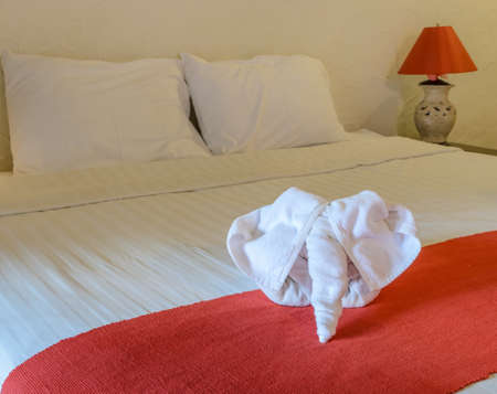 thai elephant: White towel in elephant shape on white bed in Thai style hotel bedroom