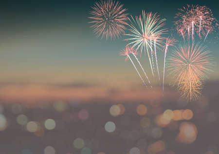 Firework on blurred twilight sky background with colorful city lights bokeh. Vintage filter effect image
