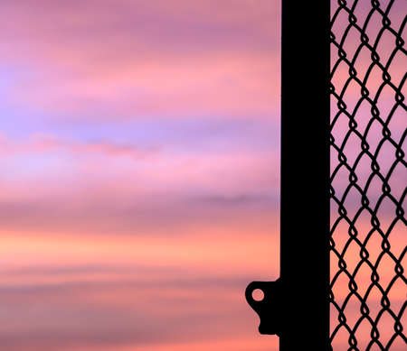 open hole: Silhouette opened mesh door with sunset background