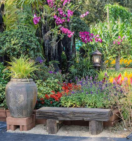 orchidee: seduta in legno e giardino di fiori decorato nel parco Archivio Fotografico
