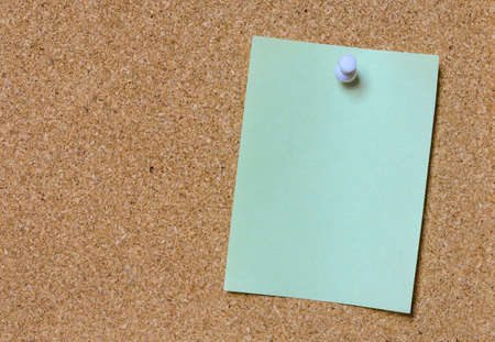 tack: Blank green paper posted on cork board with white tack pin for text and background