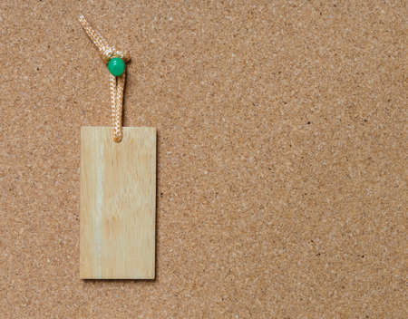 tack: Blank wooden tag hang on cork board with green tack pin for text and background Stock Photo