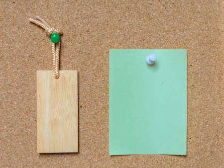 tack: Blank wooden tag ang green paper on cork board with tack pin for text and background Stock Photo