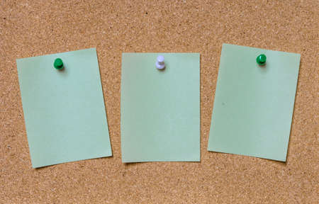 tack: Blank green paper posted on cork board with tack pin for text and background Stock Photo