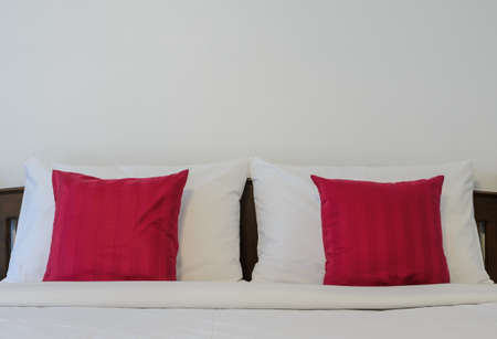 king size: White bedroom with tidy King size bed and red pillows