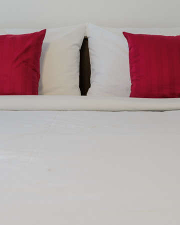 tidy: White bedroom with tidy King size bed and red pillows