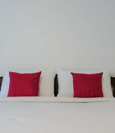 red pillows: White bedroom with tidy King size bed and red pillows