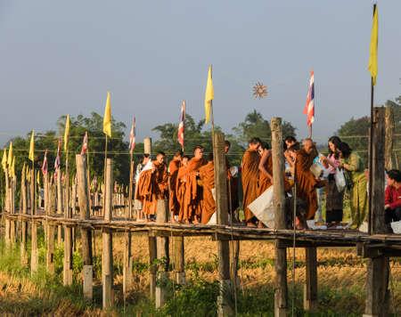 almsgiving: MAE HONG SON, THAILAND - NOVEMBER 21, 2015: Morning Buddhist Almsgiving at Zu Tong Pae bamboo bridge in Mae Hong Son, Thailand.  Monks  go on a daily almsround to collect food. Editorial