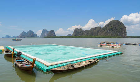 Green floating football pitch with beautiful limestone mountains background at Panyi island or Koh Panyee, floating fishing village in Phang Nga Province, Thailand Stock Photo