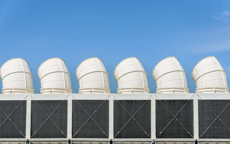 Industrial cooling towers or air cooled chillers against blue sky Stockfoto