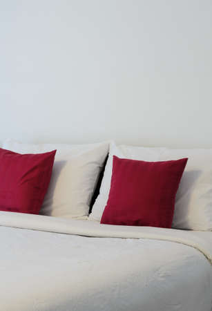red pillows: White bedroom with tidy bed and red pillows