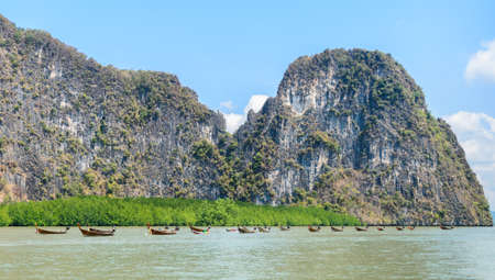 Landscapes of limestone island with mangrove forest and long-tail wooden boats in Phang Nga Bay National Park, Thailand