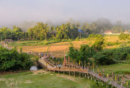 almsgiving: MAE HONG SON, THAILAND - NOVEMBER 21, 2015: Morning Buddhist Almsgiving at Zu Tong Pae bamboo bridge in Mae Hong Son, Thailand.  Monks  go on a daily almsround to collect food. Stock Photo