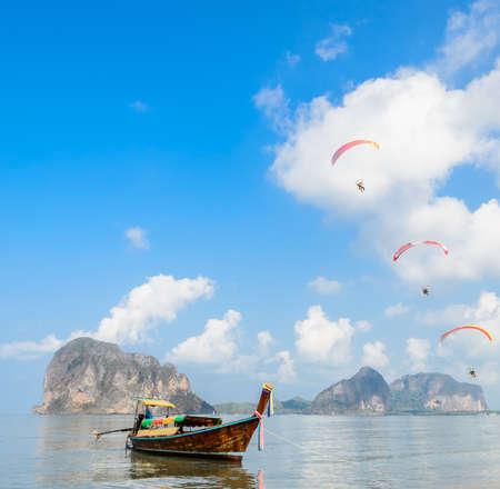 Het zeegezicht van de kalksteenberg en houten lang-staartboot met Deltaplaning over het Strand van Pak Meng in Trang-provincie, Thailand Stockfoto