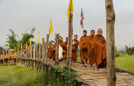 MAE HONG SON, THAILAND - NOVEMBER 21, 2015: Morning Buddhist Almsgiving at Zu Tong Pae bamboo bridge in Mae Hong Son, Thailand.  Monks  go on a daily almsround to collect food. Editorial