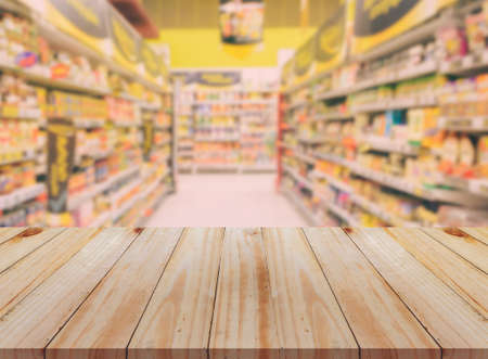 Empty wooden table with blurred supermarket background. For product display business concept.