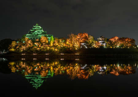 Stunning night view of Okayama castle or Crow castle illuminated on the Asahi River in autumn, Japan Stock Photo