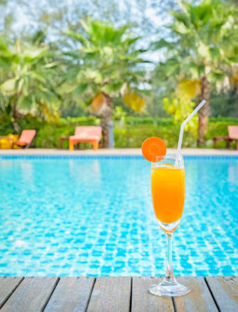 Orange juice with carrot slice in cocktail glass at outdoor swimming pool, summer tropical holiday concept Stock Photo