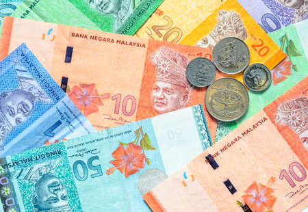 Malaysia currency of Malaysian ringgit banknotes and coins background. Sen coins of fIve, ten, twenty and fifty on paper money of one, five, ten, twenty, fifty and hundred ringgit notes. Standard-Bild
