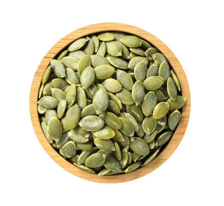 Dry pumpkin seeds in wooden bowl isolated on white background, top view on wooden. Healthy food concept