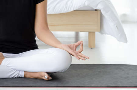 Attractive Asian woman wearing sportswear  practicing meditation yoga on mat in white bedroom, doing Accomplished Pose or Siddhasana asana in the morning. Healthcare concept of calm and relax with Yoga posture exercise