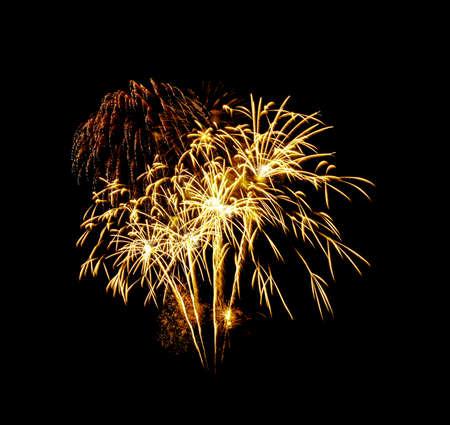 Beau feu d'artifice doré explosant dans le ciel nocturne, isolé sur fond noir. Concept de nouvel an et anniversaire.