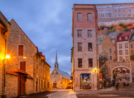 Quebec, Canadá - 16 de octubre de 2018: Vista temprano en la mañana de la iglesia de Notre-Dame-des-Victoires y murales de la ciudad de Quebec en la Place Royale de la vieja ciudad de Quebec, Canadá.