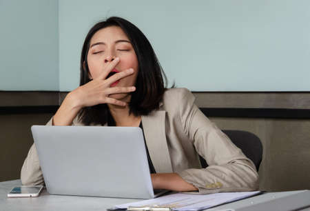 Young Asian business woman covering opened mouth with hand while yawning at meeting room in front of laptop, , feeling sleepy and bored. Overwork and sleep deprivation concept