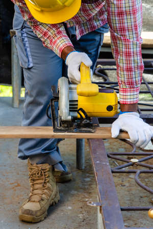Carpenter wearing safety helmet and cutting wooden board with handheld circular saw. Wood working with personnel protection concept.