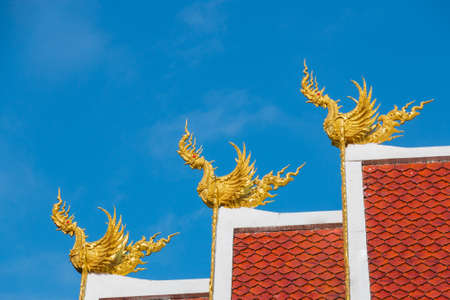 himmapan: Three Golden Himmapan Hongsa statue over the buddhist church roof in daylight  Stock Photo