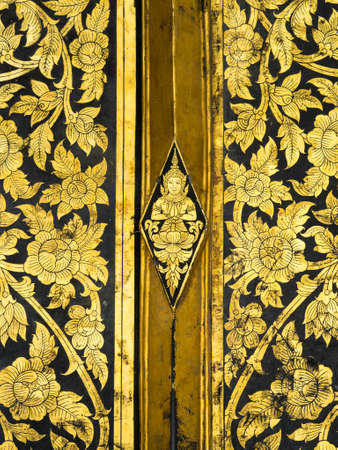 classic art: Thai classic art on temple door at Wat Rakhangkhositraram Bangkok Thailand. This use the gilding gold leave on the black lacquer method.