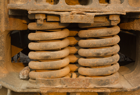 shocks: A trio of heavy-duty springs on the side of a freight train Stock Photo