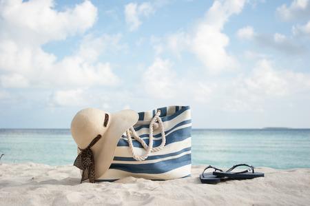 beachbag: beach bag , hat and flip flops on sand in maldives Stock Photo