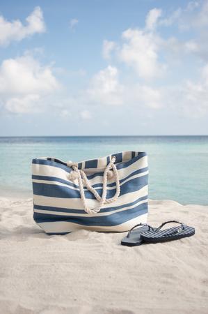beachbag: beach bag  and flip flops on sand in maldives Stock Photo