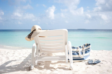 beachbag: sun lounge on a beach with hat and bag, fluffy clouds