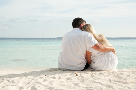 couple sittng on sand facing ocean in Mldives photo