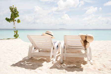 beachbag: two sun loungers facing the sea with sun hats on them Stock Photo