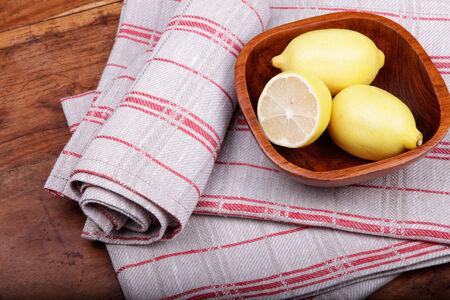 dishcloth: linen tea towel and lemons on the wooden table. Stock Photo