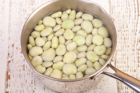 bean family: boild broad beans in the pan on wooden table