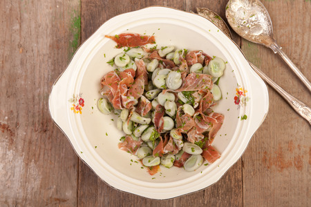parma ham: broad beans salads with parma ham on old wooden table