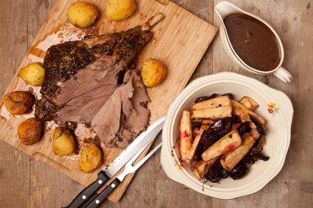 roast leg of lamb with roast vegetables and gravy Stock Photo
