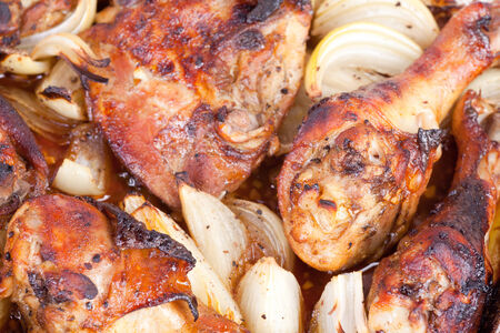 cooked chicken drumsticks with onions photo