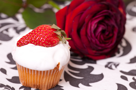 srawberry: cup cake decorated with srawberry on background with the rose. Stock Photo
