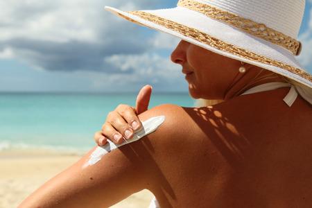 piel humana: Mujer joven que aplica Crema de sol en la playa