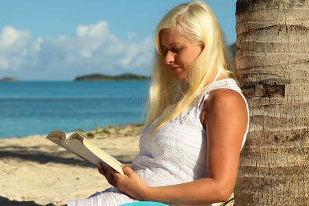 palm reading: blonde woman sitting by palm tree and reading a book Stock Photo